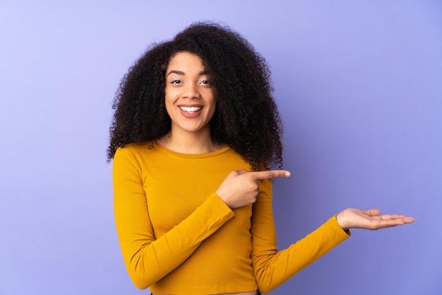 Młoda afroamerykanin kobieta na białym tle na fioletowy trzymając copyspace wyimaginowany na dłoni, aby wstawić reklamę