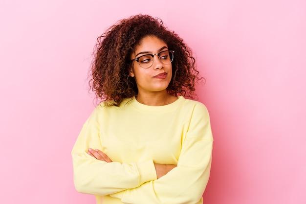 Młoda afroamerykanin kobieta na białym tle na różowej ścianie marzy o osiągnięciu celów i celów
