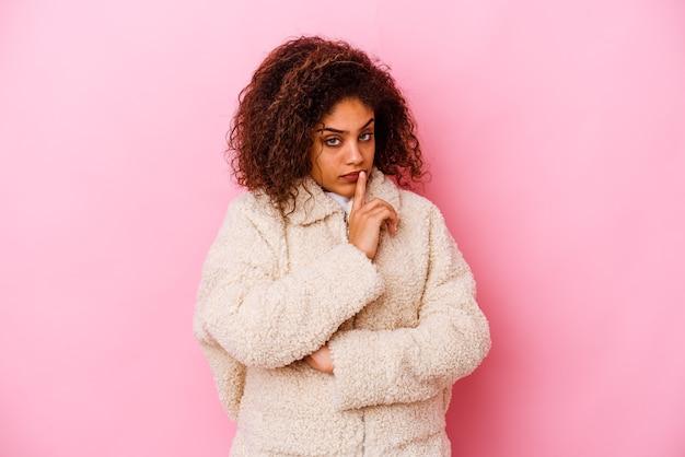 Młoda afroamerykanin kobieta na białym tle na różowej ścianie niezadowolona z sarkastycznego wyrazu.