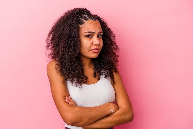 Młoda afroamerykanin kobieta na białym tle na różowej ścianie niezadowolony, patrząc z sarkastycznym wyrazem.