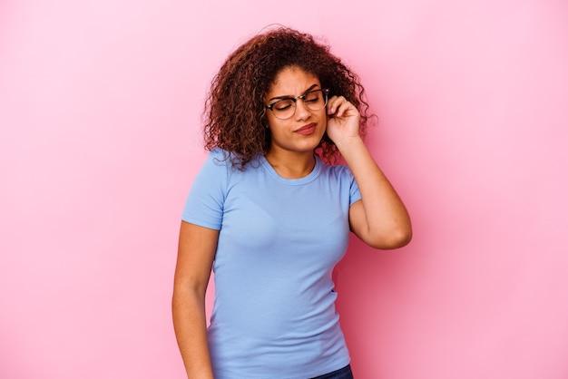 Młoda afroamerykanin kobieta na białym tle na różowej ścianie zakrywającej uszy palcami, zestresowana i zdesperowana głośnym otoczeniem.