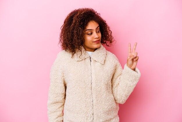 Młoda afroamerykanin kobieta na białym tle na różowym tle radosna i beztroska pokazująca palcami symbol pokoju.