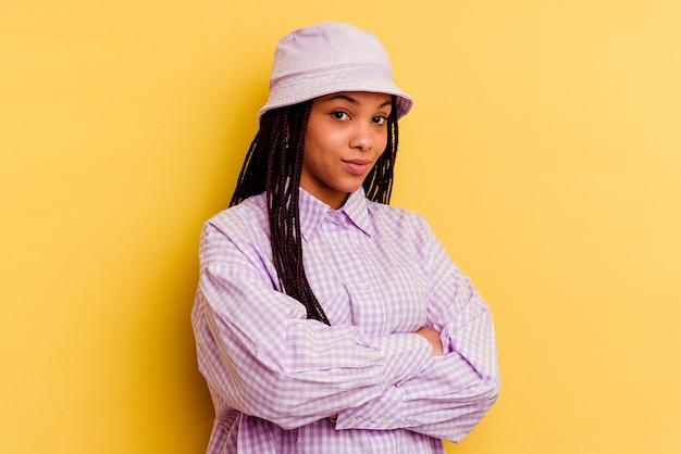 Młoda afroamerykanin kobieta na białym tle na żółtej ścianie niezadowolony, patrząc z sarkastycznym wyrazem.