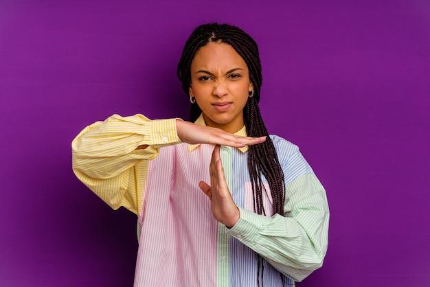 Młoda afroamerykanin kobieta na białym tle na żółtej ścianie pokazujący gest limitu czasu.