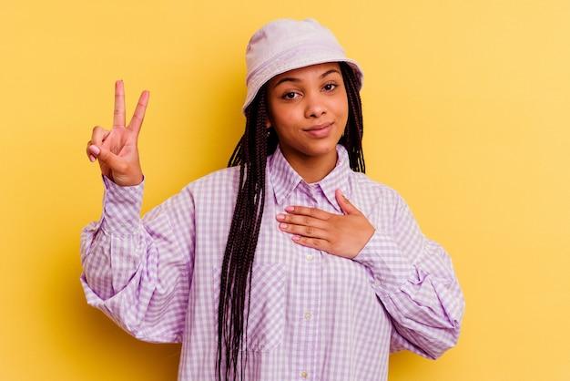 Młoda afroamerykanin kobieta na białym tle na żółtej ścianie, składając przysięgę, kładąc rękę na klatce piersiowej.