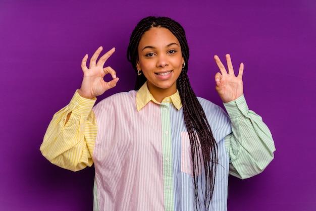 Młoda afroamerykanin kobieta na białym tle na żółtej ścianie, wesoły i pewny siebie, pokazując ok gest.