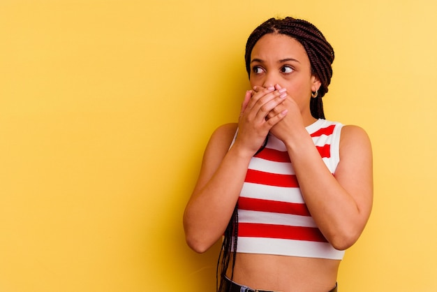 Młoda afroamerykanin kobieta na białym tle na żółtej ścianie zamyślony patrząc na przestrzeń kopię obejmującą usta ręką.