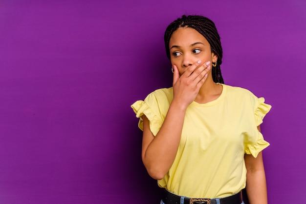 Młoda afroamerykanin kobieta na białym tle na żółtej ścianie zamyślony patrząc na przestrzeń kopię obejmującą usta ręką