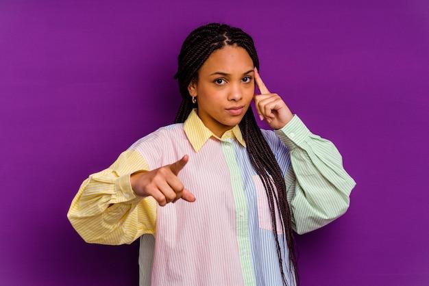 Młoda afroamerykanin kobieta na białym tle na żółtym tle, wskazując świątynię palcem, myśląc, koncentruje się na zadaniu.