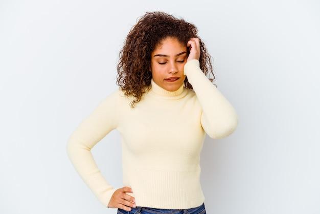 Młoda afroamerykanin kobieta na białym tle zmęczona i bardzo senna, trzymając rękę na głowie.