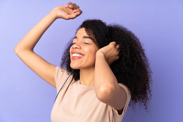 Młoda afroamerykanin kobieta na fioletowym tle słuchania muzyki i tańca
