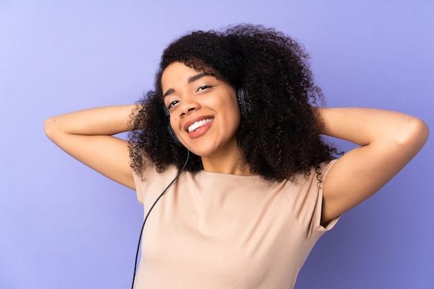 Młoda afroamerykanin kobieta na fioletowym tle słuchania muzyki