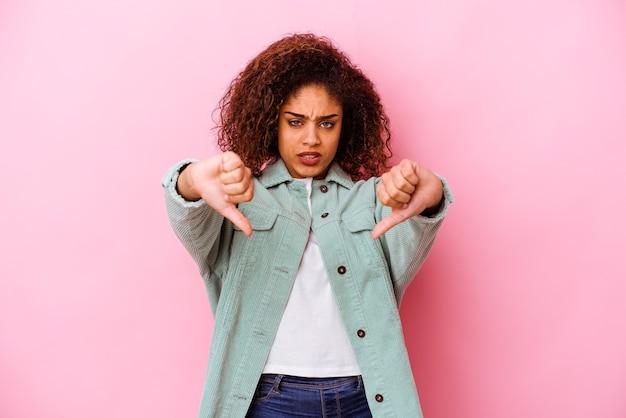 Młoda afroamerykanin kobieta na różowo pokazując kciuk w dół i wyrażając niechęć.