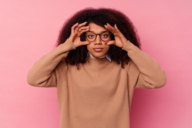 Młoda afroamerykanin kobieta odizolowana na różowej ścianie, trzymając oczy otwarte, aby znaleźć szansę na sukces.