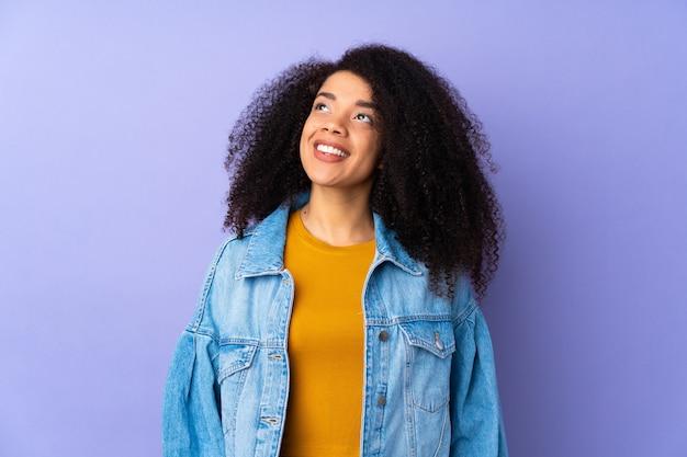 Młoda afroamerykanin kobieta odizolowywająca na fioletowym myśli pomysł, patrząc w górę