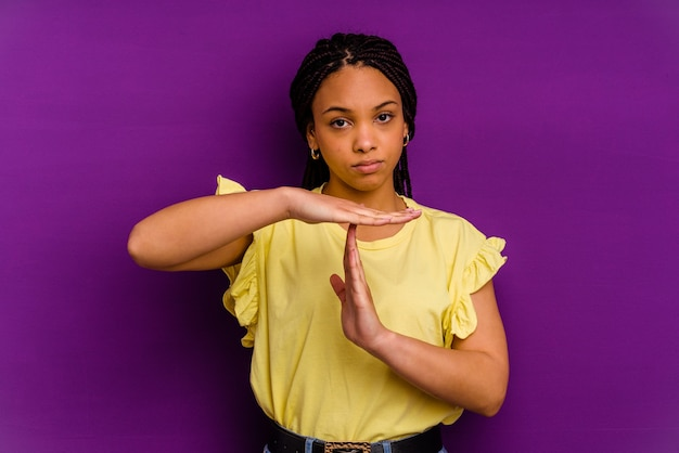 Młoda afroamerykanin kobieta odizolowywająca na żółtym przedstawiająca gest limitu czasu.