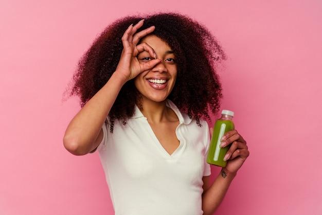 Młoda afroamerykanin kobieta pije zdrowy koktajl na białym tle na różowym tle podekscytowany utrzymując ok gest na oko.