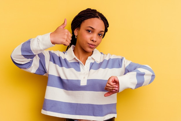 Młoda afroamerykanin kobieta pokazuje kciuki w górę i w dół, trudno wybrać koncepcję