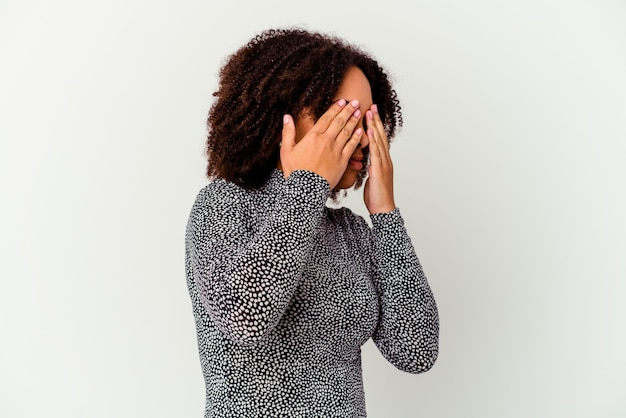 Młoda afroamerykanin kobieta rasy mieszanej na białym tle boi się obejmujące oczy rękami