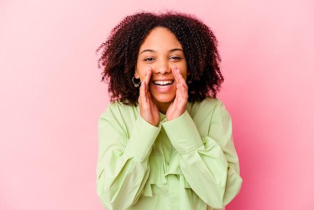 Młoda afroamerykanin kobieta rasy mieszanej na białym tle mówiąc plotkę, wskazując na bok zgłaszając coś.