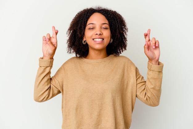 Młoda afroamerykanin kobieta rasy mieszanej na białym tle skrzyżowanie palców za szczęście