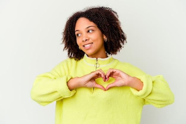 Młoda afroamerykanin kobieta rasy mieszanej na białym tle uśmiechając się i pokazując kształt serca rękami.