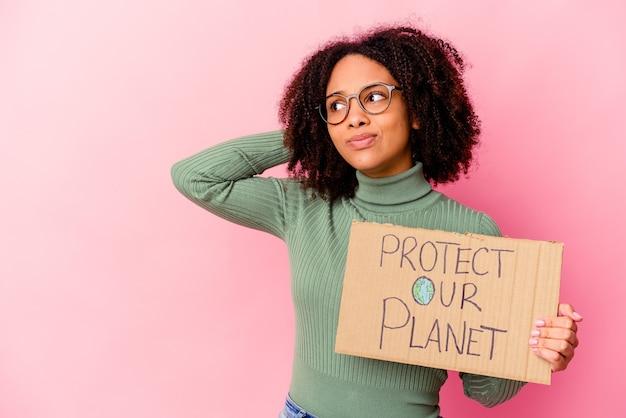 Młoda afroamerykanin kobieta rasy mieszanej trzyma karton ochrony naszej planety dotykając tyłu głowy, myśląc i dokonując wyboru.