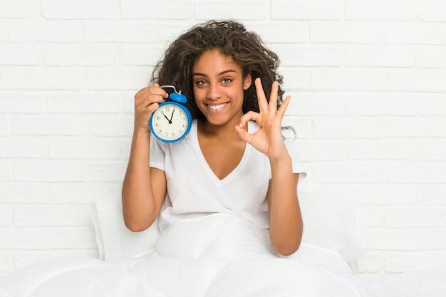 Młoda afroamerykanin kobieta siedzi na łóżku, trzymając budzik, wesoły i pewny siebie, pokazując ok gest.