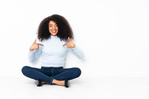 Młoda afroamerykanin kobieta siedzi na podłodze dumny i zadowolony z siebie
