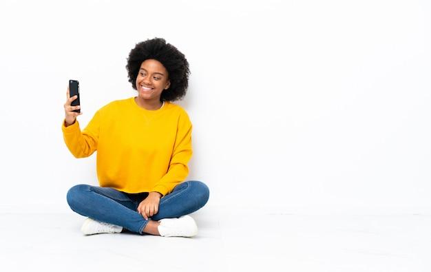 Młoda afroamerykanin kobieta siedzi na podłodze, dzięki czemu selfie