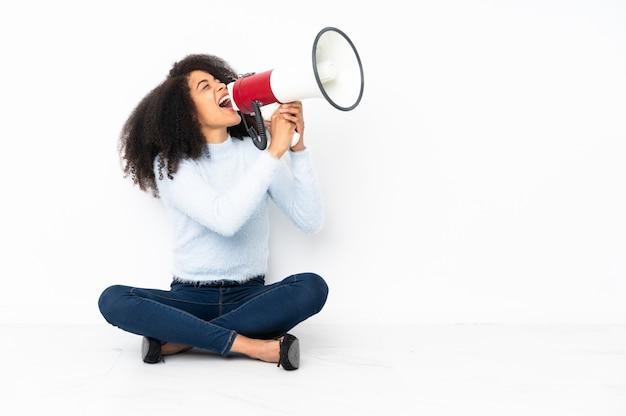 Młoda afroamerykanin kobieta siedzi na podłodze krzycząc przez megafon