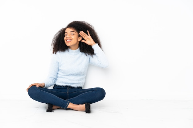 Młoda afroamerykanin kobieta siedzi na podłodze, słuchając czegoś, kładąc rękę na uchu