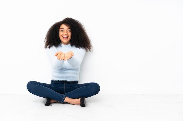 Młoda afroamerykanin kobieta siedzi na podłodze trzymając copyspace wyimaginowany na dłoni, aby wstawić reklamę