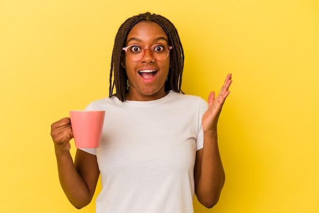 Młoda afroamerykanin kobieta trzyma kubek na białym tle na żółtym tle zaskoczony i zszokowany.