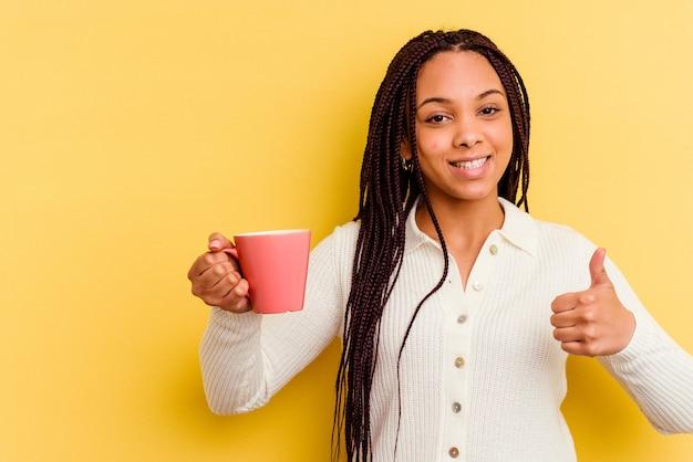 Młoda afroamerykanin kobieta trzyma kubek na białym tle, uśmiechając się i podnosząc kciuk do góry