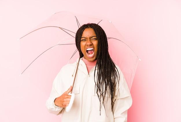 Młoda afroamerykanin kobieta trzyma parasol na białym tle krzycząc bardzo zły i agresywny.