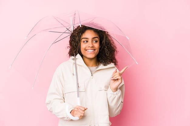 Młoda afroamerykanin kobieta trzyma parasol, uśmiechając się i wskazując na bok, pokazując coś w pustej przestrzeni.
