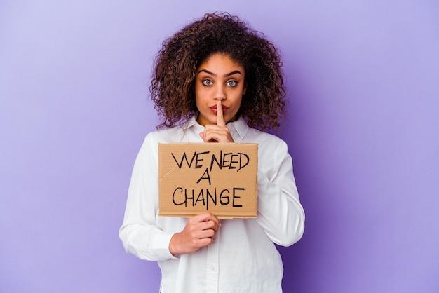 Młoda afroamerykanin kobieta trzyma tabliczkę zmiany na białym tle na fioletowym tle, zachowując tajemnicę lub prosząc o ciszę.