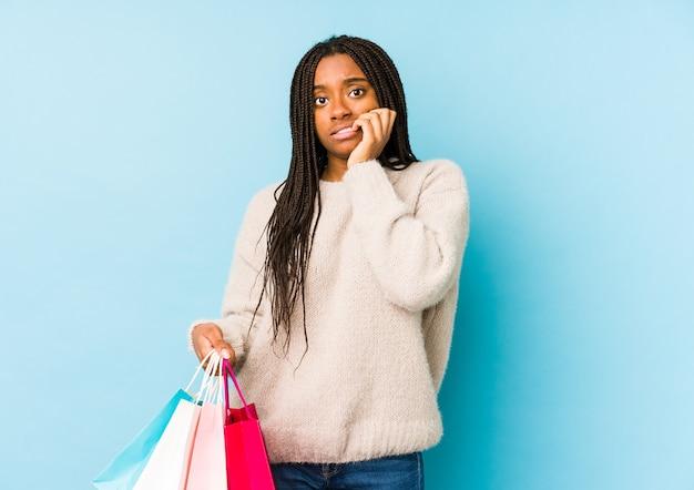 Młoda afroamerykanin kobieta trzyma torbę na zakupy na białym tle obgryzając paznokcie, nerwowy i bardzo niespokojny.