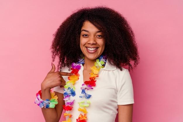 Młoda afroamerykanin kobieta ubrana w hawajską osobę, wskazując ręką na miejsce na kopię koszuli, dumna i pewna siebie