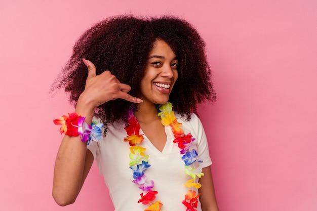 Młoda afroamerykanin kobieta ubrana w hawajskie rzeczy pokazujący gest rozmowy telefonicznej palcami.