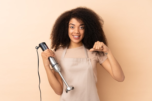 Młoda afroamerykanin kobieta za pomocą blendera na beżowym tle dumny i zadowolony z siebie