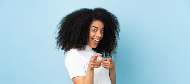 Młoda afroamerykanin kobieta zdziwiona i wskazująca przód