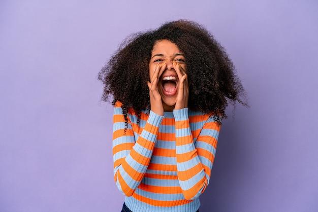 Młoda afroamerykanin kręcone kobieta na białym tle na fioletowej ścianie, krzycząc podekscytowany do przodu.