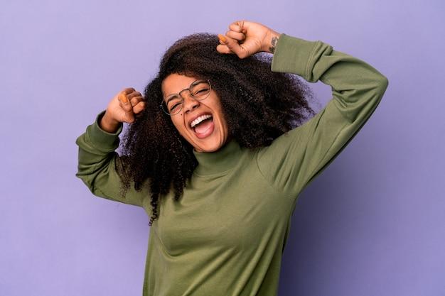 Młoda afroamerykanin kręcone kobieta na białym tle na fioletowej ścianie świętuje specjalny dzień, skacze i podnosi ręce z energią.