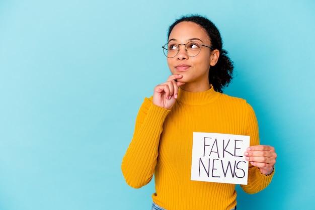 Młoda afroamerykanin kręcone kobieta trzyma karton z wiadomością