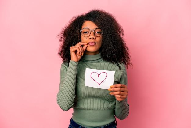 Młoda afroamerykanin kręcone kobieta trzyma symbol serca na afisz z palcami na ustach, zachowując tajemnicę.