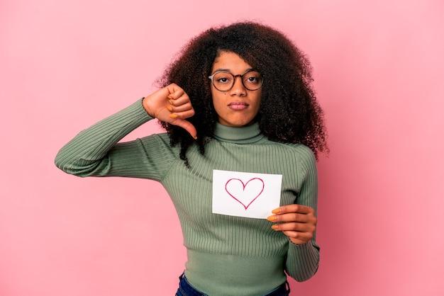 Młoda afroamerykanin kręcone kobieta trzyma symbol serca na afiszu, pokazując gest niechęci, kciuki w dół. pojęcie sporu.