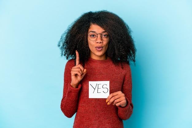 Młoda afroamerykanin kręcone kobieta trzyma tabliczkę tak, mając świetny pomysł, pojęcie kreatywności.