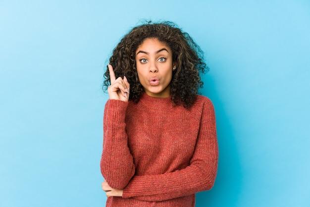 Młoda afroamerykanin kręcone włosy kobieta ma jakiś świetny pomysł, pojęcie kreatywności.